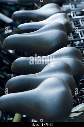 Close up of saddles on new bicycles for sale outside shop in Berlin Germany - Stock Image