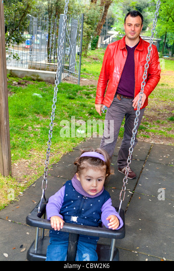 Father pushing daughter on a swing - Stock Image