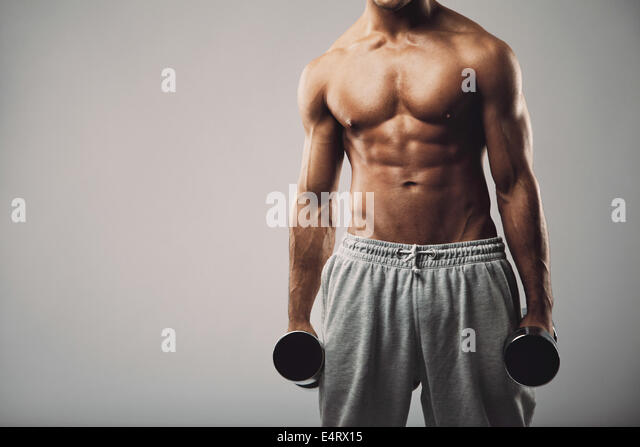 Studio shot of a male model in sweatpants holding dumbbells in both hands on grey background with copy space. Shirtless - Stock Image