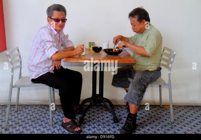 Singapore Horne Road restaurant Asian man eating table - Stock Image