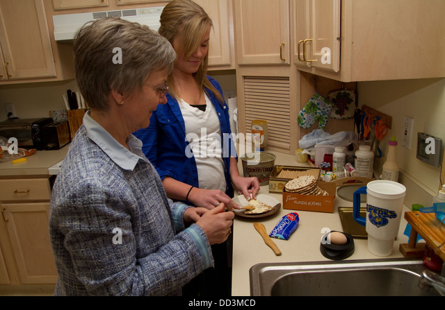 Mother and daughter together in the kitchen making a snack. Swedish-Americans in Lindsborg, Kansas. - Stock Image