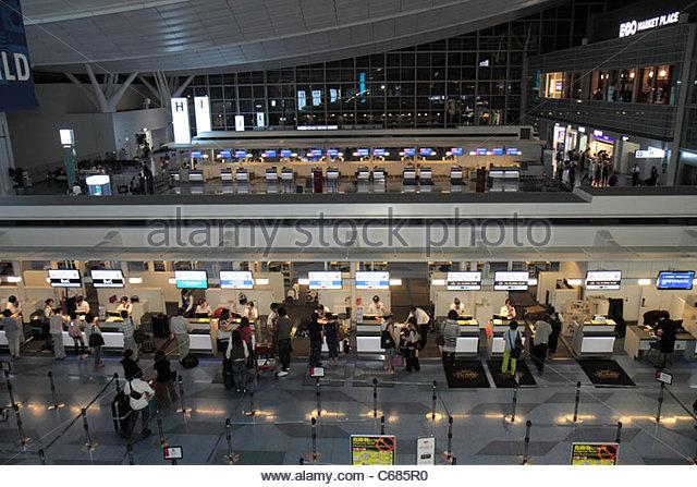 Japan Tokyo Haneda Airport Japan Airlines kanji hiragana katakana characters symbols Japanese English check-in agent - Stock Image