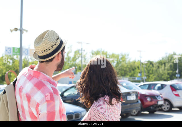 Man showing something to woman on city street against clear sky - Stock Image