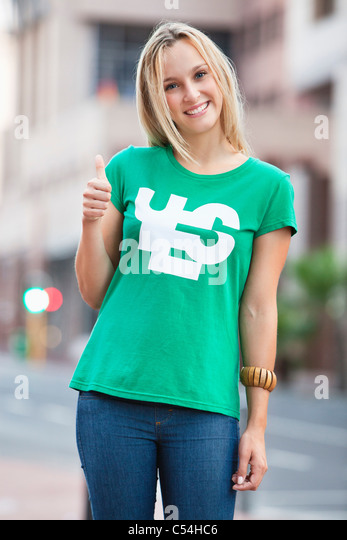 Portrait of beautiful woman showing thumbs up sign - Stock Image