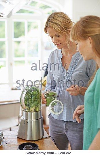 Women preparing green vegan smoothie in kitchen - Stock Image