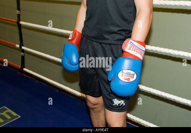 Boxer in gloves standing in ring - Stock Image