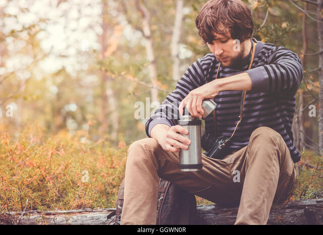 Traveler Man relaxing in forest with thermos, backpack and photo camera Travel Lifestyle concept vacations outdoor - Stock Image