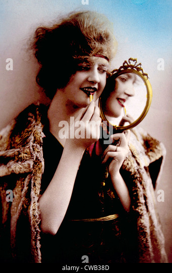 Women holding mirror while applying lipstick, circa. 1900. - Stock-Bilder