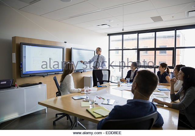 Businessman leading meeting at monitor in conference room - Stock Image