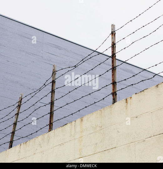 Barbed wire fence at  top of a wall in a city. - Stock Image