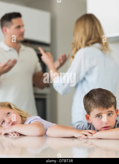 Sad children leaning on table while parents arguing - Stock Image