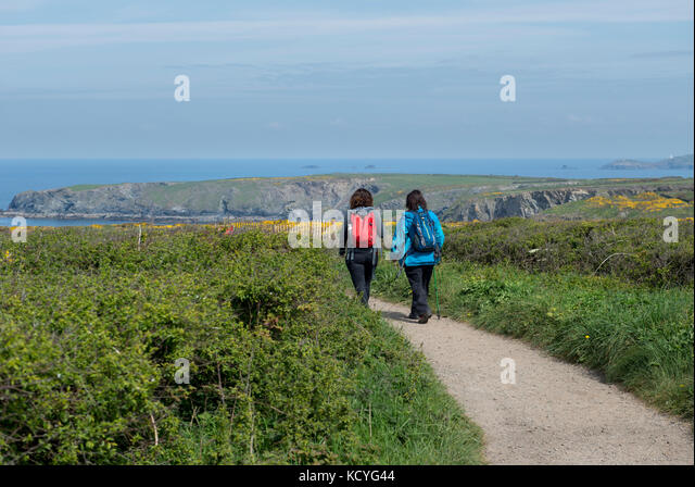 Two women walking along the South West Coast Path near Tintagel in Cornwall, England, UK - Stock Image