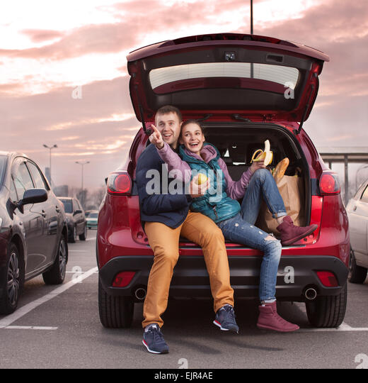 Happy couple sitting at car trunk after shopping - Stock Image