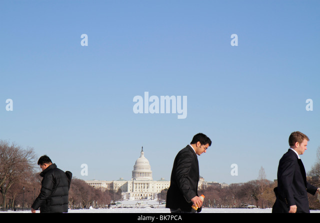 Washington DC The National Mall US Capitol Building man walking snow winter cold weather coat - Stock Image