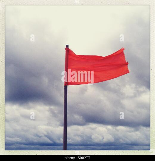A red flag blowing at an ocean front beach. No swimming allowed - Stock Image