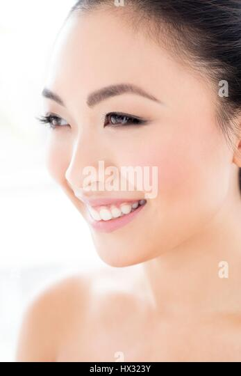 MODEL RELEASED. Young Asian woman looking away smiling, portrait. - Stock-Bilder