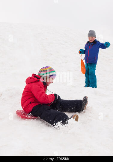 small girl sledging down a steep hill with small boy watching in background - Stock Image