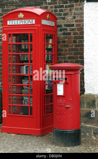 An old red British Telephone box turned into a British village eccentric lending library , next to a working post - Stock Image