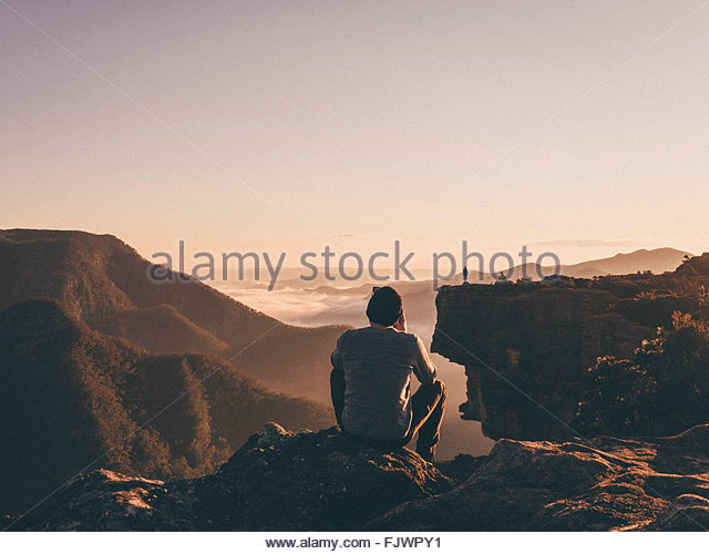 Rear View Of Man Sitting On Rock At Mountain Against Sky - Stock Image