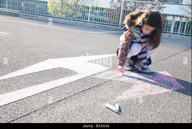 young girl drawing arrow in opposite direction of road sign - Stock Image