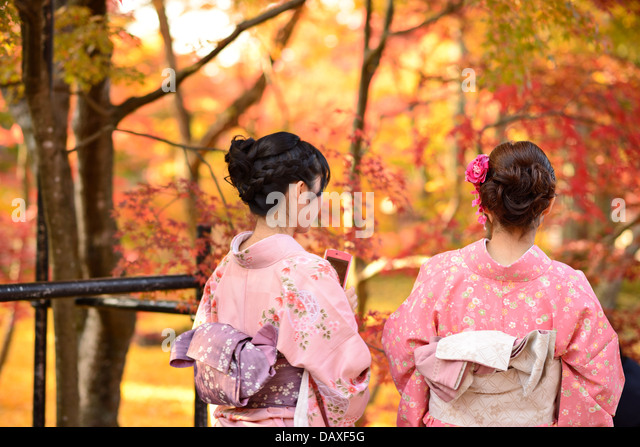 Girls view fall foliage in Kyoto, Japan. - Stock Image