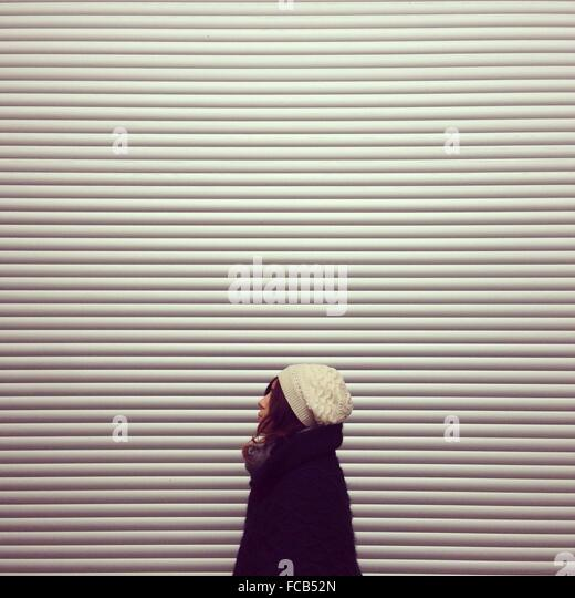 Side View Of Woman Standing Against Closed Shop - Stock Image