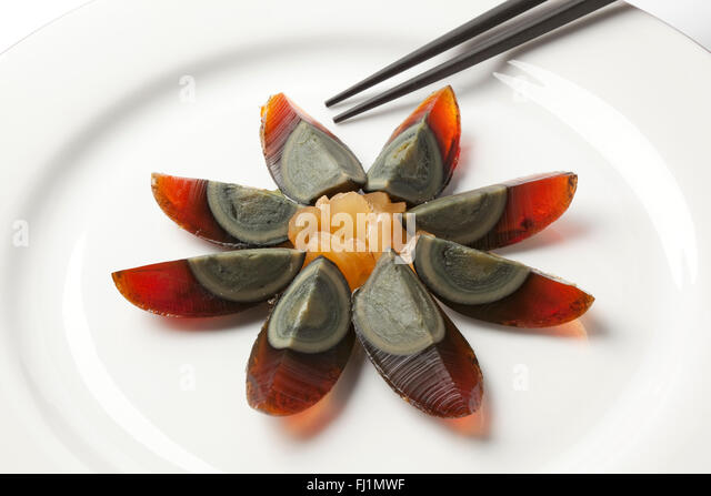 Thousand years duck egg with ginger on a plate - Stock Image
