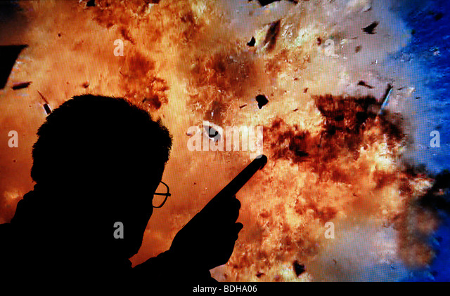 terrorist with gun and explosion - Stock Image