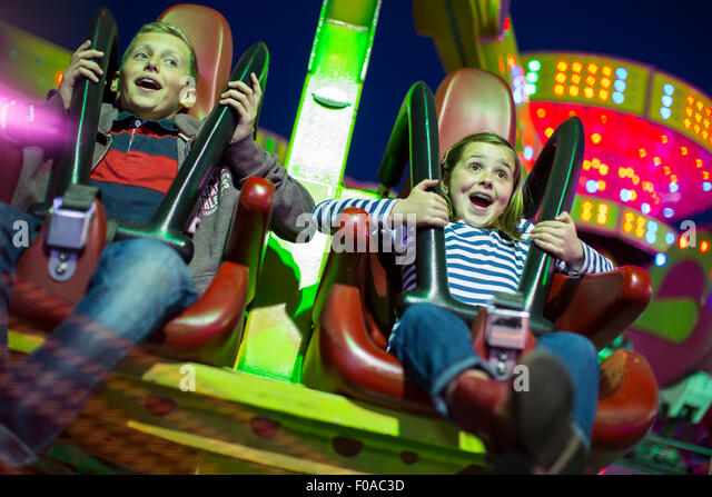 Sister and brother on fairground ride at night - Stock Image