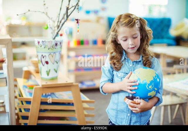 Student examining globe in classroom - Stock Image