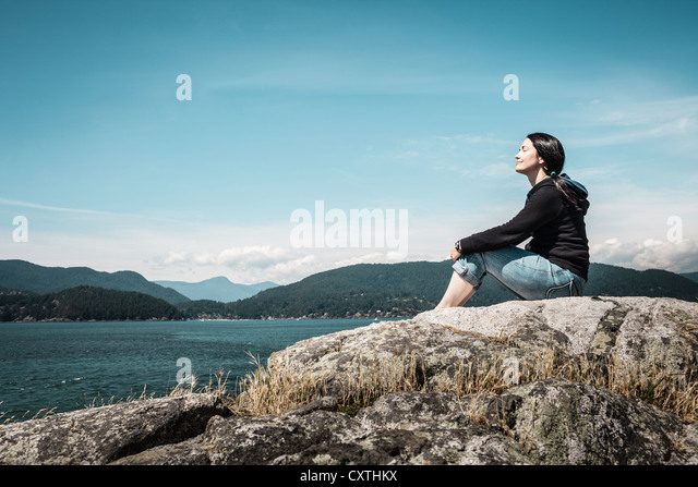 Woman relaxing by rural lake - Stock Image