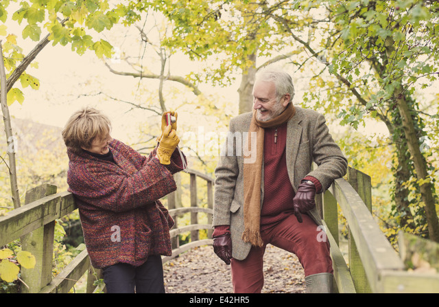 Mature woman photographing senior man - Stock Image