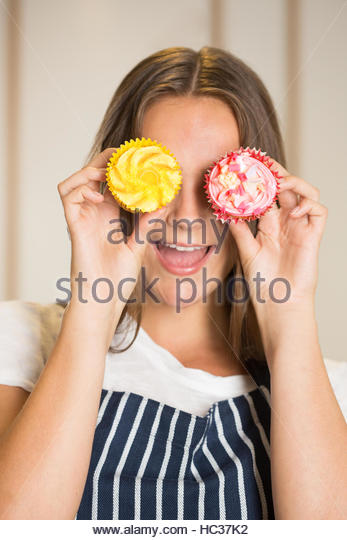 Woman holding cup cakes in front of eyes - Stock Image