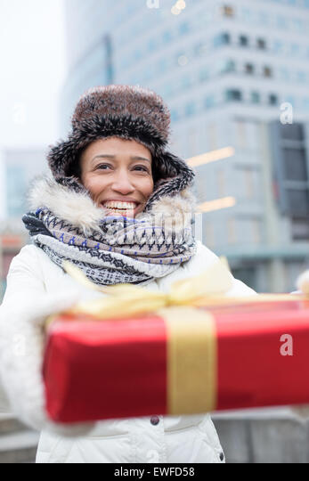 Happy woman holding gift during winter in city - Stock Image