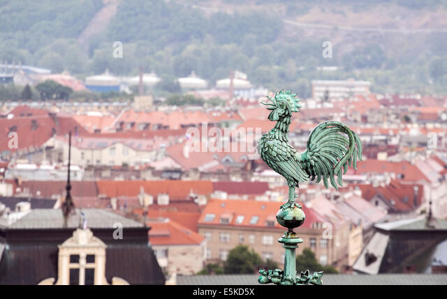 Rooster overlooking Prague roofs - Stock Image