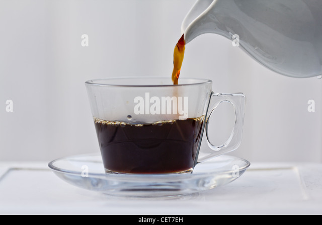 Pouring coffee into a half full clear cup with a saucer. - Stock Image