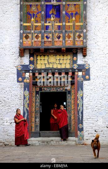 Monks of the Drukpa monastic community entering the courtyard of Trashigang Dzong fortress, Trashigang, Trashigang - Stock Image