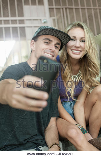 Young man and woman taking self portrait using smartphone - Stock-Bilder