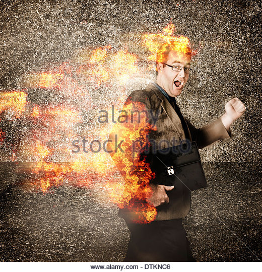 Funny portrait of a time driven businessman running engulfed in fire with a crazy look of stress. Rush hour - Stock Image
