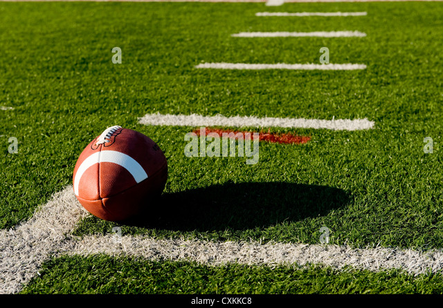 A brown leather American football on a green football field - Stock Image