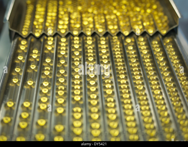 Rows of vitamin capsules in pharmaceutical factory - Stock Image