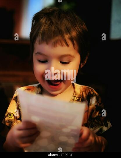 Happy Girl Reading Letter At Home - Stock Image