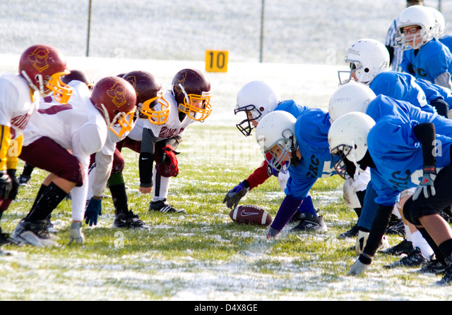 Boys age 10 playing football in early October snowfall. St Paul Minnesota MN USA - Stock Image