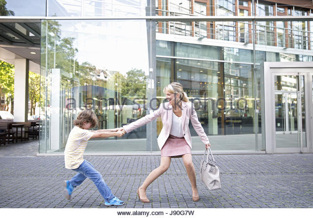Businesswoman Pulling Reluctant Son Along Outside Office - Stock-Bilder