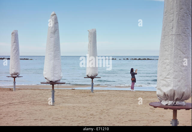 Young woman photographing sea with smartphone, Pescara, Abruzzo, Italy - Stock Image