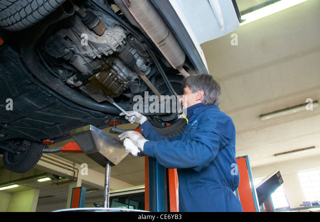 mechanic repairs a car in a garage - Stock Image