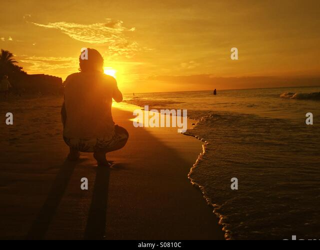 Taking a picture of the sunset on the beach - Stock Image
