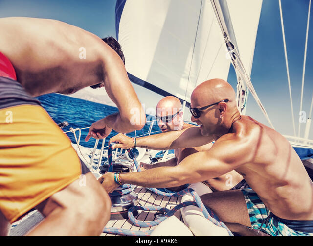 Group of handsome shirtless sailors working on sailboat, involved in maritime competition, enjoying water sport - Stock Image