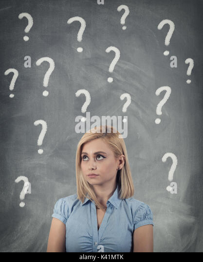 Thinking business woman looking up on many questions mark isolated on gray wall background - Stock Image