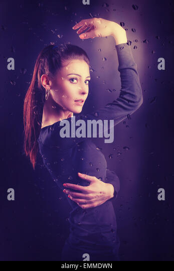 Vintage portrait af a beautiful woman through rainy glass. - Stock-Bilder